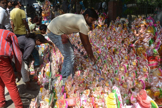 Indians shop for idols of the Hindu god Lord Ganesh ahead of the Ganesh Chaturthi festival in New Delhi on September 7, 2013. The Hindu festival which celebrates the rebirth of the God Lord Ganesha, begins this year on September 9 and culminates on September 19, with many of the statues being immersed in bodies of water. (Photo by AFP Photo/Raveendran)