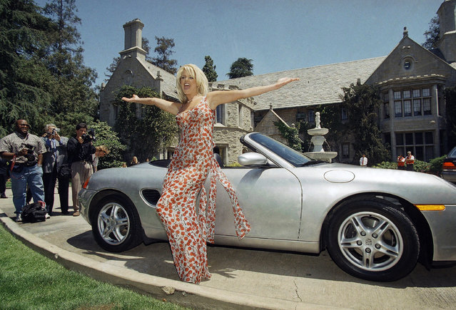 File - In this May 1, 1997, file photo, Victoria Silvstedt poses with her brand new Porsche in front of the Playboy Mansion in Beverly Hills, Calif. The Playboy Mansion is up for sale but longtime resident Hugh Heffner wants to stay put. Playboy Enterprise announced the West Los Angeles estate, the backdrop of many film shoots and wild parties, was listed on Monday, January 11, 2016, for $200 million. (Photo by Chris Pizzello/AP Photo)