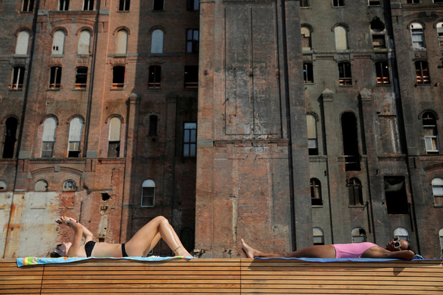 Women lie in the sun in Domino Park as high temperatures hit the region in Brooklyn, New York, U.S., August 29, 2018. (Photo by Andrew Kelly/Reuters)