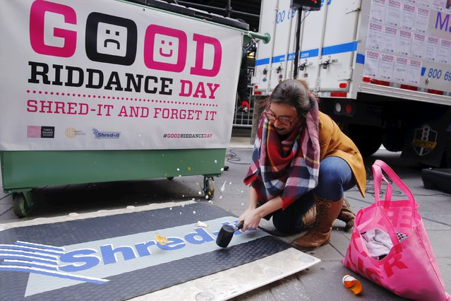 """A woman uses a hammer to destroy prescription pill containers during  """"Good Riddance Day"""" in New York December 28, 2015. Good Riddance Day is an event held in New York just before New Years Eve for people to shred pieces of paper representing their bad memories or things they want to get rid of before the New Year. (Photo by Lucas Jackson/Reuters)"""