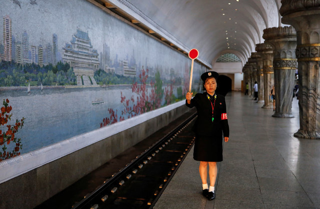 A railway worker gives a signal as the train leaves a subway station in Pyongyang, North Korea on September 11, 2018. (Photo by Danish Siddiqui/Reuters)
