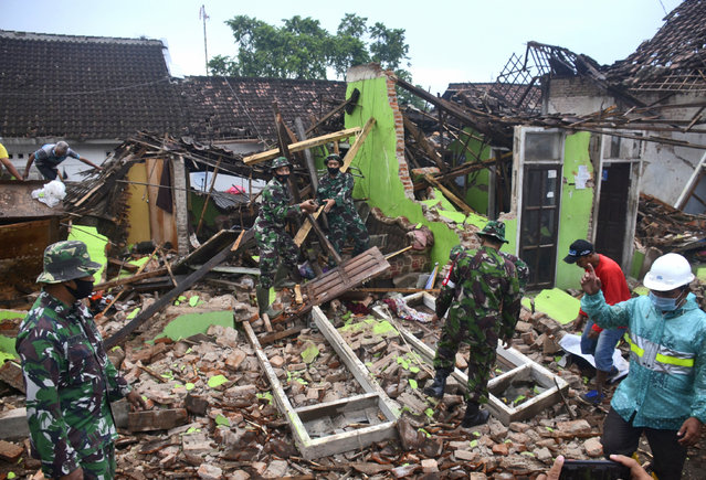 Indonesian soldiers help clear up rubble at a house damaged by an earthquake in Malang, East Java, Indonesia, Sunday, April 11, 2021. The deadly earthquake on Indonesia's main island of Java damaged multiple buildings, officials said Sunday. It didn't trigger a tsunami. (Photo by Hendra Permana/AP Photo)