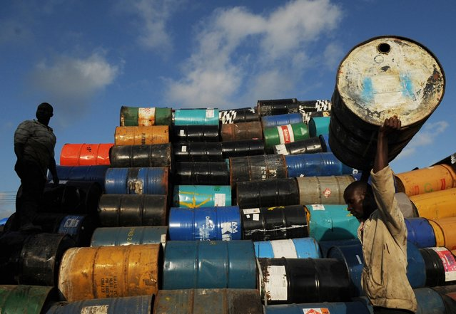 Men stack oil barrels at a depot in Santo Domingo February 6, 2015. A group of resident Haitians sell the metal barrels for $9 each to be used as garbage bins, or made into grills or to store water. (Photo by Ricardo Rojas/Reuters)