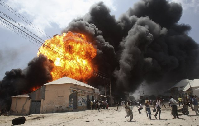 People run away from an explosion at a petrol station and storage facility near the Bakara open-air market in Somalia's capital Mogadishu, February 23, 2015. (Photo by Ismail Taxta/Reuters)