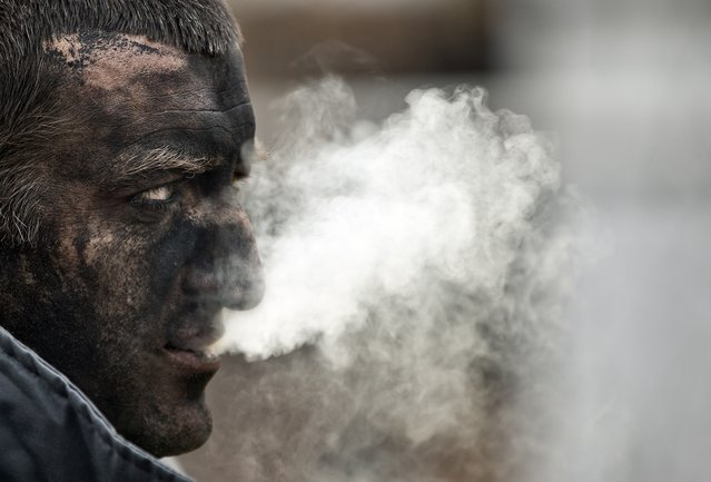 A Ukrainian mining rescuer smokes after taking part in the search for bodies of miners  killed in an explosion yesterday before dawn at more than 1,000 metres (3,200 feet) underground at the Zasyadko mine, in Donetsk, Ukraine, Thursday, March 5, 2015.Officials in a separatist rebel-held city in east Ukraine say the death toll from an accidental explosion at a coal mine has risen to 32, while one person still remains unaccounted for. (AP Photo/Vadim Ghirda)