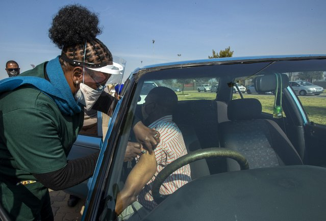 Health workers vaccinates a pensioner with a first dose of the Pfizer coronavirus vaccine at the newly-opened mass vaccination program for the elderly at a drive-thru vaccination center in Johannesburg, South Africa, Tuesday, May 25, 2021. (Photo by Themba Hadebe/AP Photo)