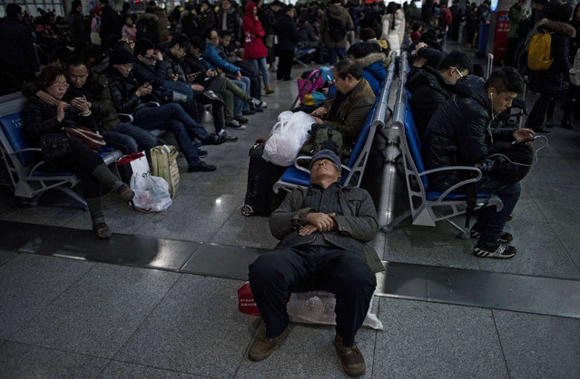 Passengers wait to board their trains as they head to their hometowns for the Lunar New Year holiday, at Shanghai railway station in Shanghai on January 29, 2016. Over 2.9 billion trips will be made around China during the 40-day Spring Festival travel rush, which kicked off on January 24, Chinese authorities estimated. (Photo by Johannes Eisele/AFP Photo)