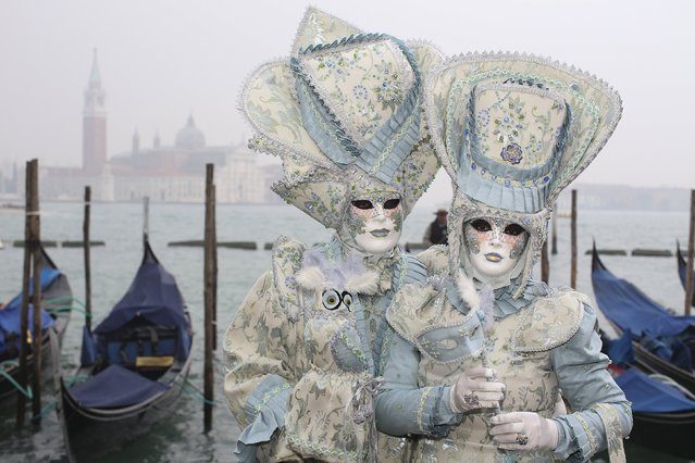 Masked revellers pose in San Marco Piazza during the Venice Carnival, January 30, 2016. (Photo by Alessandro Bianchi/Reuters)