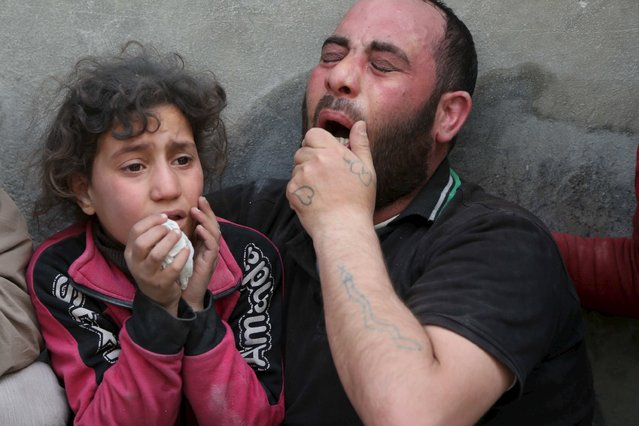 A father and his daughter mourn the loss of their relatives to what activists say was a barrel bomb dropped by forces loyal to Syria's President Bashar al-Assad, in Aleppo's al-Fardous district April 29, 2015. (Photo by Hosam Katan/Reuters)