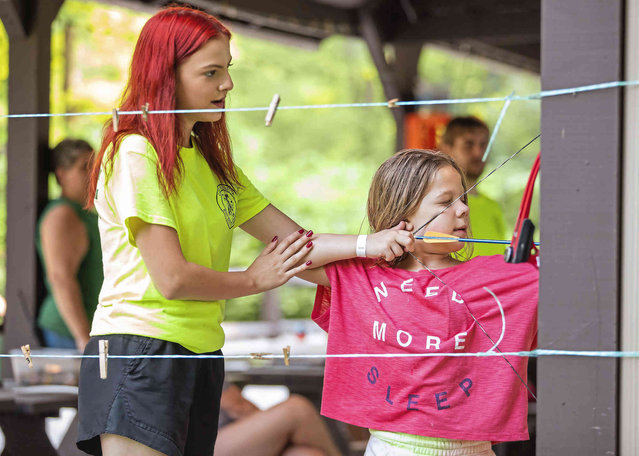 Counselor Paris Wohlgemuth helps Effie, 8, aim her bow during an archery activity at the STEM Adventure Day Camp at Boy Scouts of America's Camp Guyasuta, Wednesday, July 7, 2021, in Sharpsburg, Pa. The camp runs for eight weeks this summer. (Photo by Andrew Rush/Pittsburgh Post-Gazette via AP Photo)
