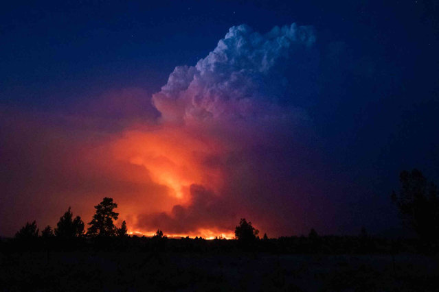 In this photo provided by the Oregon Office of State Fire Marshall, flames and smoke rise from the Bootleg fire in southern Oregon on Wednesday, July 14, 2021. The largest fire in the U.S. on Wednesday was burning in southern Oregon, to the northeast of the wildfire that ravaged a tribal community less than a year ago. The lightning-caused Bootleg fire was encroaching on the traditional territory of the Klamath Tribes, which still have treaty rights to hunt and fish on the land, and sending huge, churning plumes of smoke into the sky visible for miles. (Photo by John Hendricks/Oregon Office of State Fire Marshal via AP Photo)