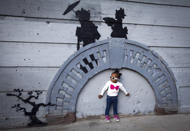 A child poses for a photo under a new art piece by British graffiti artist Banksy in the Brooklyn borough of New York, October 17, 2013. (Photo by Carlo Allegri/Reuters)