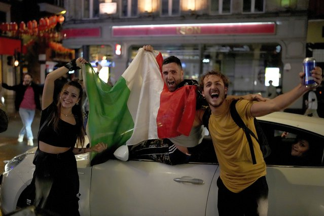 Italian fans celebrate in central London, in the early hours of Monday, July 12, 2021, after Italy won the Euro 2020 soccer championship final match between England and Italy played at Wembley Stadium. (Photo by Matt Dunham/AP Photo)