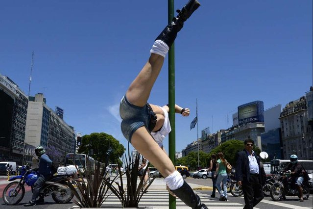 A participant in the Miss Pole Dance South America 2013 competition performs in front of the obelisk in Republica Square in downtown Buenos Aires on November 22, 2013 ahead of the contest to be held on November 23 and 25 in the city. (Photo by Juan Mabromata/AFP Photo)