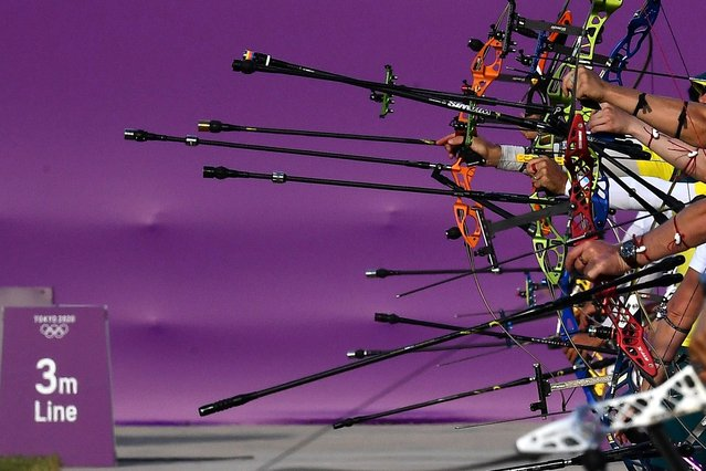Archers hold their bows during a day of ranking at the Yumenoshima Park Archery Field ahead of the Tokyo 2020 Olympic Games on July 21, 2021 in Tokyo, Japan. (Photo by Clodagh Kilcoyne/Reuters)