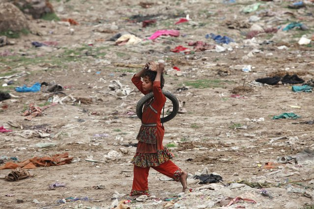 A girl carries a broken brick on her head while walks along a littered ground in Lahore's slum, February 16, 2015. (Photo by Mohsin Raza/Reuters)
