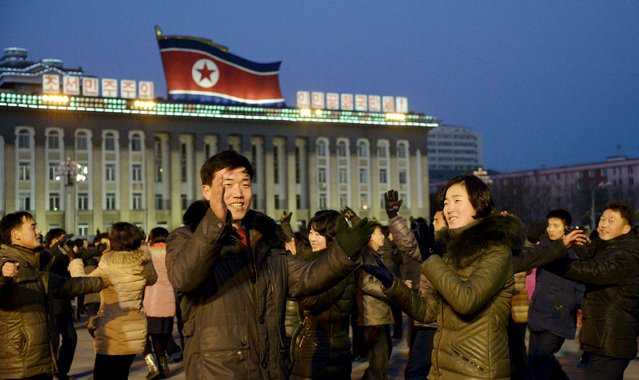 """North Koreans dance to celebrate what the country claims was a """"successful hydrogen bomb"""" test at Kim Il Sung square in Pyongyang, North Korea, in this photo released by Kyodo January 8, 2016. South Korea unleashed a high-decibel propaganda barrage across its border with North Korea on Friday in retaliation for its nuclear test, while the United States called on China to end """"business as usual"""" with its ally. (Photo by Reuters/Kyodo News)"""