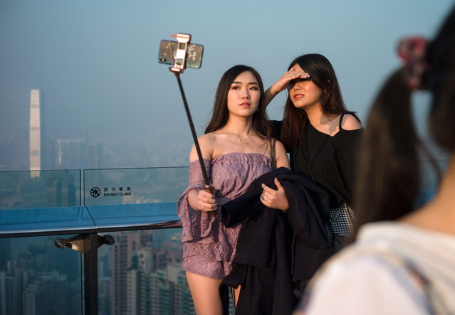 Tourists take photos from a panoramic viewing deck on Victoria Peak in Hong Kong, China, 26 January 2019. Hong Kong has been ranked the world's freest economy by the Heritage Foundation, a conservative research and educational institution based in Washington, for the 25th consecutive year, but the researchers also said the judiciary had become less effective. (Photo by Jerome Favre/EPA/EFE)