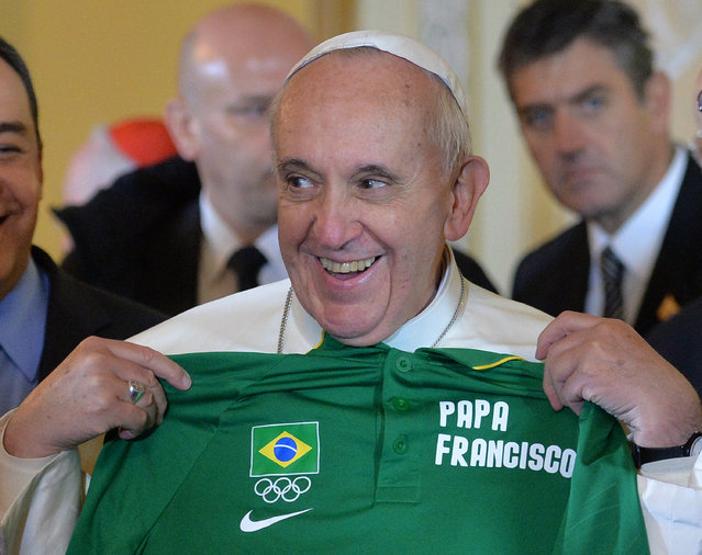 Pope Francis holds up an Olympic T-shirt with his name on it given to him in Rio de Janeiro, Brazil, Thursday, July 25, 2013. (Photo by Luca Zennaro/AP Photo)