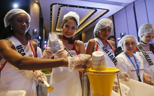 Miss Universe contestants, from left, Deshauna Barber of the United States, Chalita Suansane of Thailand, Jayathi De Silva of Sri Lanka and Dijana Cvijetic of Switzerland, help pack meals for distribution to the needy in suburban Pasay city southeast of Manila, Philippines Wednesday, January 18, 2017. (Photo by Bullit Marquez/AP Photo)