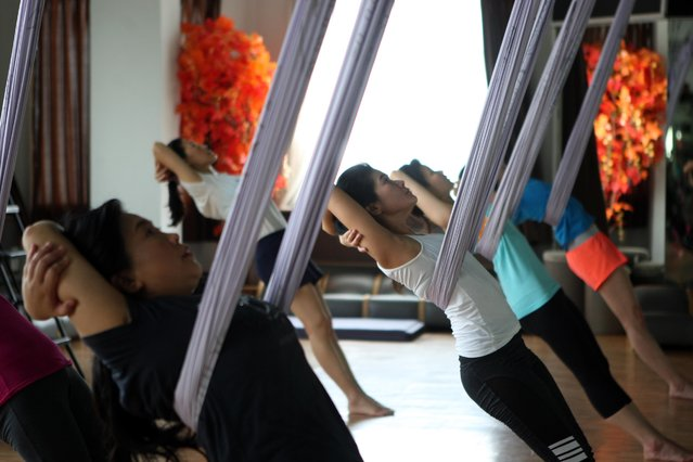 Some women stretching using hammocks as they attend the Anti-Gravity yoga class at Svarga e-Motion Sanctuary at Dharmawangsa Square, Jakarta, Saturday, April 18, 2015. (Photo by Jurnasyanto Sukarno/JG Photo)