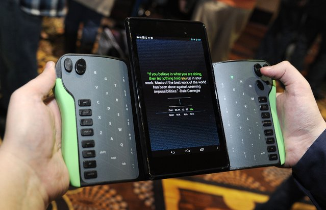 "Robert Price of TREWGrip LLC demonstrates a TREWGrip handheld rear-type keyboard and air mouse for Apple and Android tablets at the ""CES: Unveiled"", media preview for International CES, at the Mandalay Bay Convention Center in Las Vegas on January 5, 2014. (Photo by Robyn Beck/AFP Photo)"