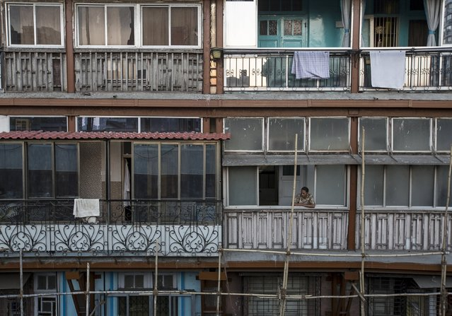A woman looks out of a window of an apartment in south Mumbai March 15, 2015. The cost for buying a 600 square feet (55 square meters) one-bedroom apartment in this building is around 20,000 Indian rupees per square feet ($ 320) or 12,000,000 Indian rupees ($ 192,000). The rent for an apartment in the same building is around 15,000 Indian rupees ($ 240) per month. (Photo by Danish Siddiqui/Reuters)
