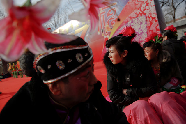 Performers try to stay warm as they wait their turn to go on stage at the Longtan park as the Chinese Lunar New Year, which welcomes the Year of the Rooster, is celebrated in Beijing, China January 29, 2017. (Photo by Damir Sagolj/Reuters)