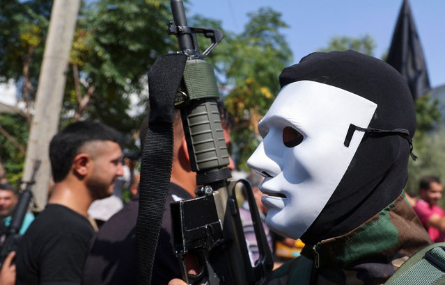 A masked Palestinian militant takes part in the funeral of member of the military wing of the Islamic Jihad group Alaa Zayoud, 22, reportedly killed in clashes with Israeli forces earlier, at his village of Silat al-Harithiyah, east of Jenin in the occupied West Bank, on September 30, 2021. (Photo by Jaafar Ashtiyeh/AFP Photo)