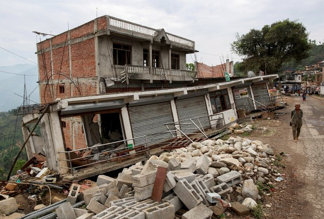 A resident walks past damaged buildings at a village following Saturday's earthquake in Sindhupalchowk, Nepal, April 28, 2015. (Photo by Danish Siddiqui/Reuters)