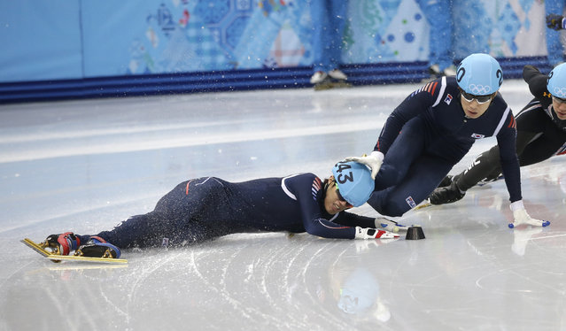 Sin Da-woon of South Korea, left, crashes as Lee Han-bin of South Korea goes down with him in a men's 1500m short track speedskating semifinal at the Iceberg Skating Palace during the 2014 Winter Olympics, Monday, February 10, 2014, in Sochi, Russia. (Photo by Darron Cummings/AP Photo)