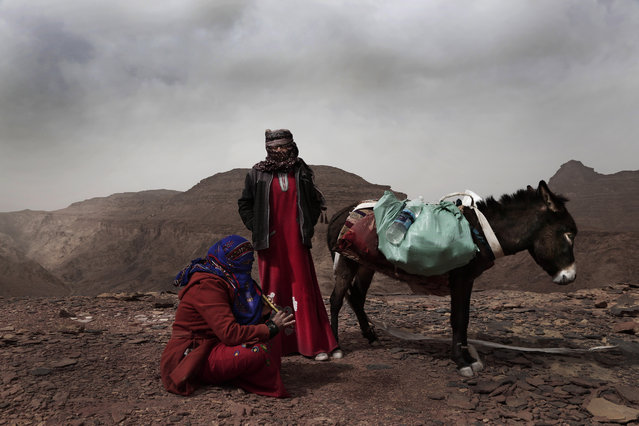 In this March 30, 2019 photo, Umm Yasser, the first Bedouin female guide from the Hamada tribe, looks at Umm Soliman as she plays the flute, near Wadi Sahw, Abu Zenima, in South Sinai, Egypt. Umm Yasser is breaking new ground among the deeply conservative Bedouin of Egypt's Sinai Peninsula. Women among the Bedouin almost never work outside the home, and even more rarely do they interact with outsiders. But Umm Yasser is one of four women from the community who for the first time are working as tour guides. (Photo by Nariman El-Mofty/AP Photo)