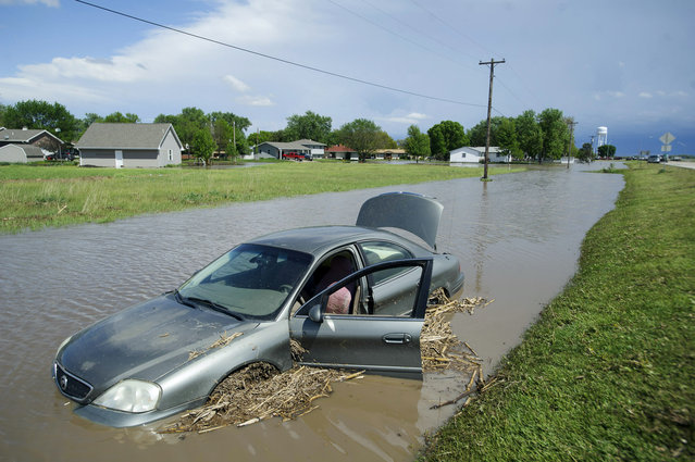 A vehicle is submerged Thursday, May 7, 2015, in De Witt, Neb. Communities in several southern Plains states set to work cleaning up Thursday after a night of storms that spawned tornadoes, assessing the damage under sunny skies but with the threat of even worse weather on the horizon. (Photo by Matt Ryerson/The Journal-Star via AP Photo)