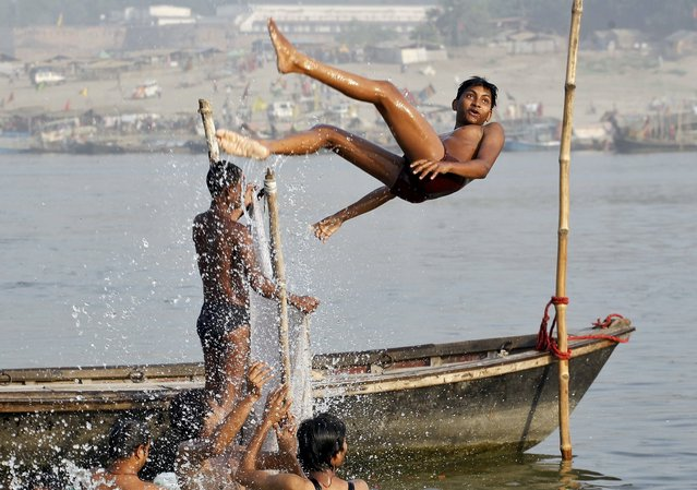 A boy somersaults as he cools off himself in the waters of the Ganges river in Allahabad, India, May 4, 2015. (Photo by Jitendra Prakash/Reuters)