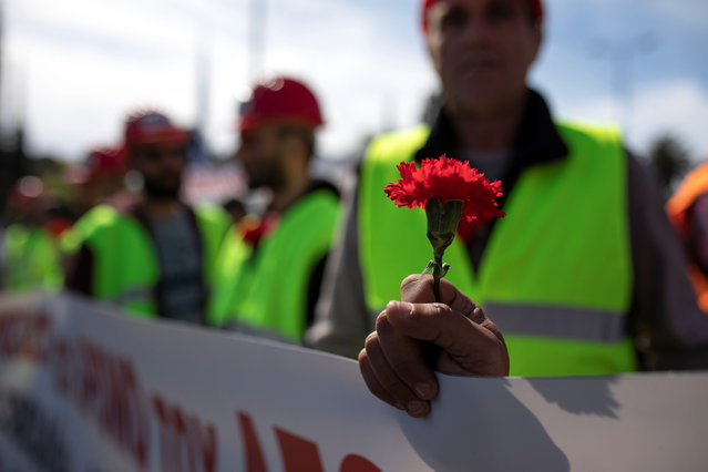 A member of the communist-affiliated PAME holds a carnation during a rally commemorating May Day in Athens, Greece, May 1, 2019. (Photo by Alkis Konstantinidis/Reuters)