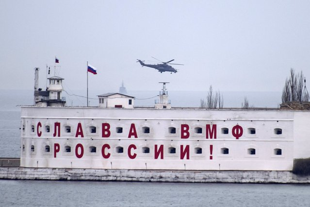 An attack helicopter, believed to Russian, flies over a Russian military base in at  Crimean port of Sevastopol March 6, 2014. (Photo by Baz Ratner/Reuters)