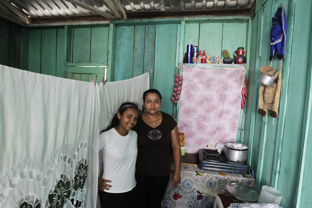 Susana Maria Cardona, 33, and her daughter Alejandra Ruby Cardona, 12, pose for a photograph inside their home in Tegucigalpa February 20, 2014. Susana Maria, who is a housewife, finished school at 17. Her ambition was to become a lawyer. She hopes that her daughter will become a doctor. Alejandra Ruby will finish education in 11 years and hopes to be an agronomist. (Photo by Jorge Cabrera/Reuters)