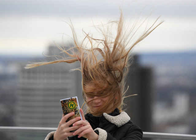 Elena from Dresden has her hair ruffled by the wind as she stands on a visitors' platform on the Maintower in Frankfurt am Main, western Germany, during stormy weather on February 22, 2017. (Photo by Arne Dedert/AFP Photo/DPA)