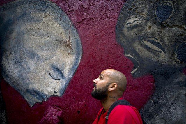 In this February 9, 2017 photo, graffiti artist Yulier Rodriguez Perez poses with one of his works, painted on a wall in Old Havana, Cuba. Three years ago, the whimsical designs of the 27-year-old artist with the signature Yulier P. began to appear on walls in Havana where graffiti is rare. (Photo by Ramon Espinosa/AP Photo)