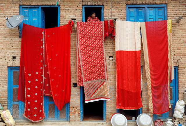 A woman looks out of the window of a house as saris, traditional clothing worn by women, are hanged out to dry in Lalitpur, Nepal on April 17, 2019. (Photo by Navesh Chitrakar/Reuters)