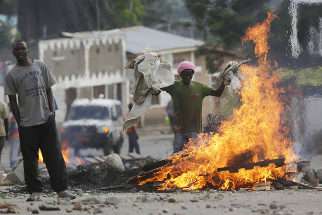 Protesters stand by a burning barricade in the Musaga neighborhood of Bujumbura, Burundi, Thursday May 21, 2015. (Photo by Jerome Delay/AP Photo)