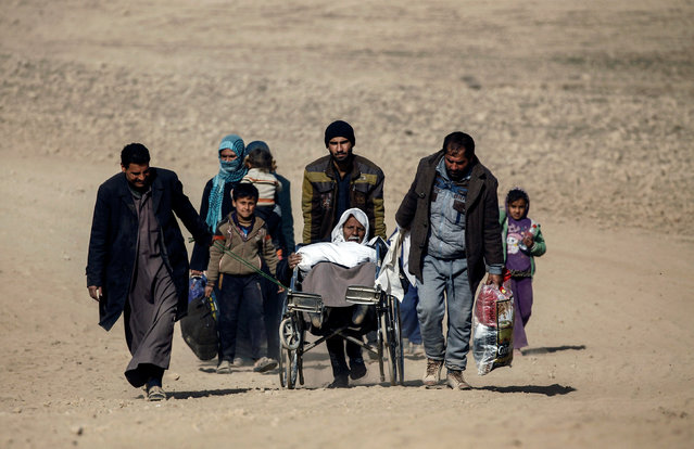 Displaced Iraqis who fled their homes walk through the desert, as Iraqi forces battle with Islamic State militants in western Mosul, Iraq, February 28, 2017. (Photo by Zohra Bensemra/Reuters)