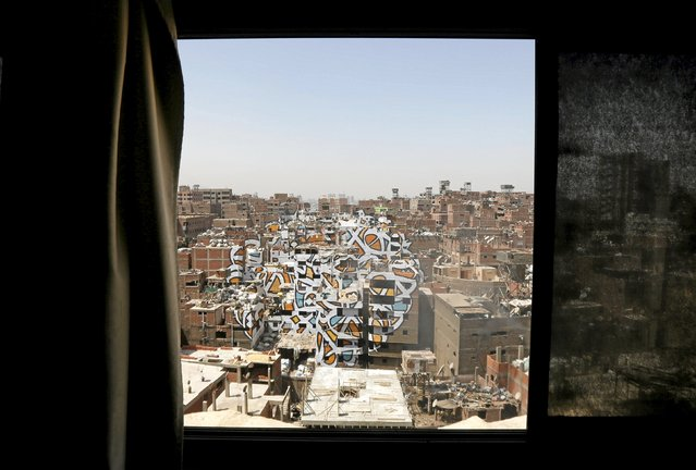 """A mural painted on the walls of houses in Zaraeeb, created by French-Tunisian artist El Seed, is seen through a window in the shanty area known as Zabaleen or """"Garbage City"""" on the Mokattam Hills in eastern Cairo, Egypt, April 4, 2016. (Photo by Amr Abdallah Dalsh/Reuters)"""
