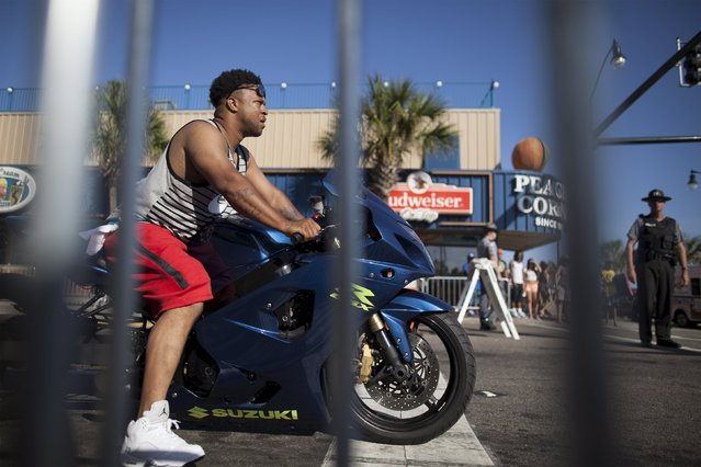 A biker is seen through the metal fencing blocking both sides of Ocean Boulevard during the 2015 Atlantic Beach Memorial Day BikeFest in Myrtle Beach, South Carolina May 24, 2015. (Photo by Randall Hill/Reuters)