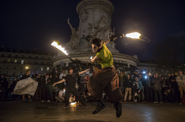 """Participants of the social media-born movement dubbed """"La Nuit Debout"""" (""""The Night awake"""" or """"The night standing up"""") watch performers on Place de la Republique, as they gather to protest against the labor law reform bill in Paris, France, 15 April 2016. The Nuit Debout movement, which began on 31 March 2016, is reminiscent of the Spanish """"Podemos"""" movement and the global """"#Occupy"""" movement – with daily general assemblies organised at sun-down. (Photo by Ian Langsdon/EPA)"""