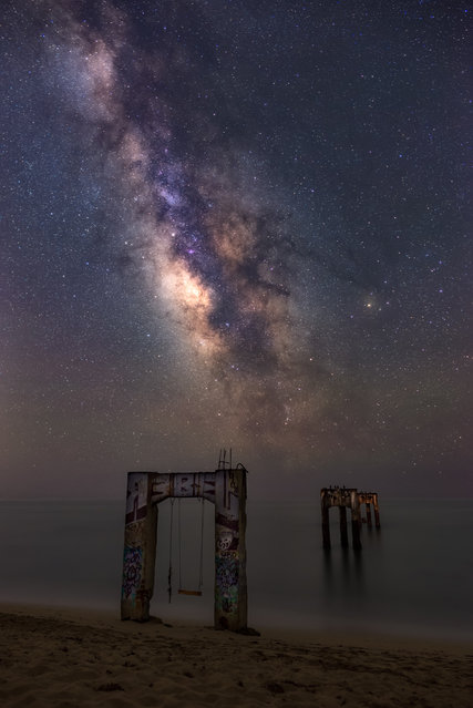 The Remnants. Marcin Zajac (Poland). The galactic centre shines bright over the Davenport pier. Built in the 1860s, the pier was a platform used for transporting timber towards San Francisco. Long abandoned since then, the wharf eroded and today only the concrete arches that once held the pier have survived the test of time. (Photo by Marcin Zajac/National Maritime Museum)