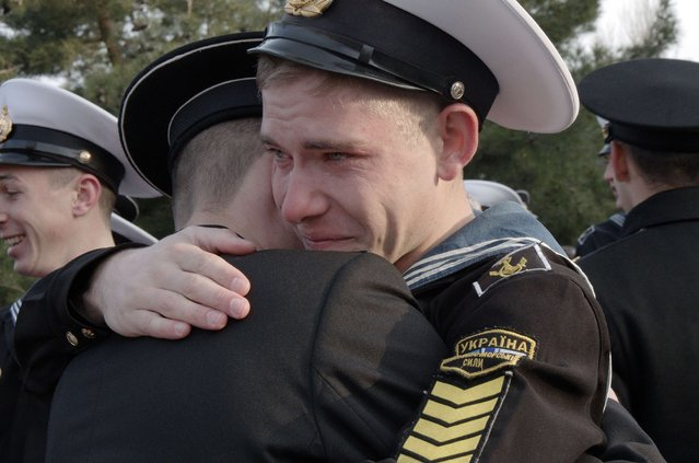 Ukrainian cadets of Higher Naval School react as they embrace with their friend who has decided to stay in education in the school during the ceremony of  departure in Sevastopol on April 4, 2014. Some 120 cadets who refused to take Russian citizenship, left the school in Crimean city of Sevastopol to Ukraine. (Photo by Vasiliy Batanov/AFP Photo)