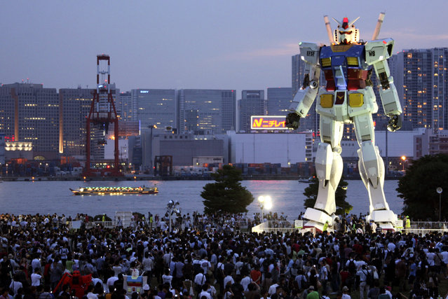 In this photo taken on July 11, 2009, people crowd to see 18-meter (60-foot) tall Gundam at a park in the manmade Odaiba island in Tokyo, Japan. If anything can encourage busy Tokyoites to take notice of their city's bid to host the 2016 Olympics, it's a replica of the popular robot animation Mobile Suit Gundam, the Japanese anime series robot, big enough to take on Godzilla. (Photo by Koji Sasahara/AP Photo)