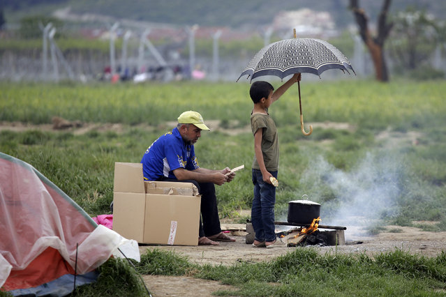 A child uses an umbrella to avoid rain falling on a fire at the northern Greek border point of Idomeni, Greece, Monday, April 25, 2016. Many thousands of migrants remain at the Greek border with Macedonia, hoping that the border crossing will reopen, allowing them to move north into central Europe. (Photo by Gregorio Borgia/AP Photo)
