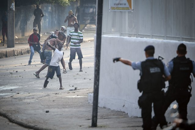Men throw stones at police that entered an abandoned building occupied by squatters to evict them in Rio de Janeiro, Brazil, on April 11, 2014. The lot, owned by a telephone company, included offices and warehouses and was occupied last week. (Photo by Yasuyoshi Chiba/AFP Photo)
